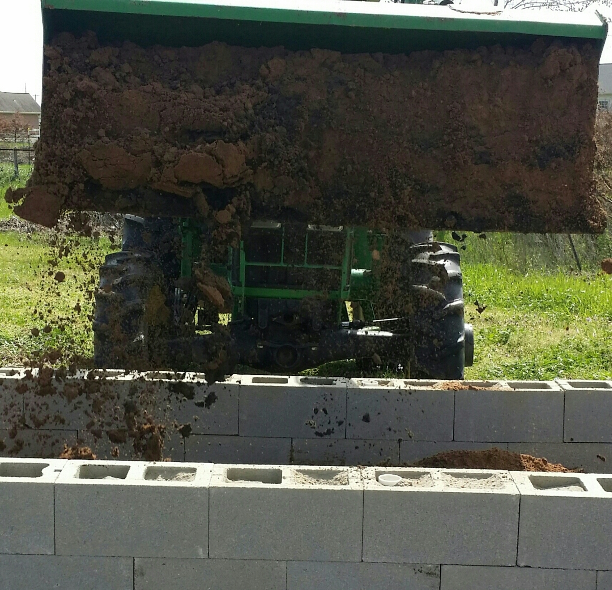Tractor bucket drops soil into the raised bed.