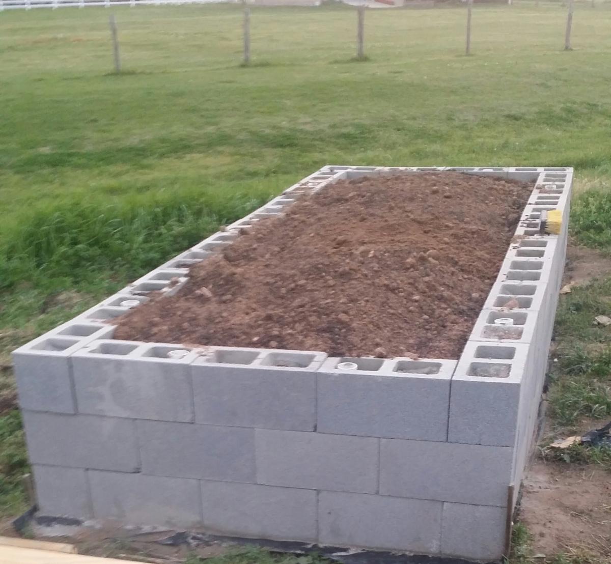 Cinder block framed raised bed filled with soil.