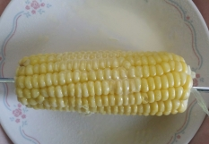 Corn on the cob shown on a saucer plate.