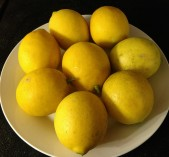 Whole Meyer lemons pictured on a plate.